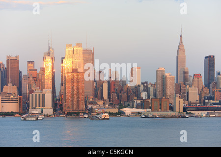 The setting sun reflects off the windows of Manhattan skyscrapers on 42nd street as viewed over the Hudson River - Stock Photo