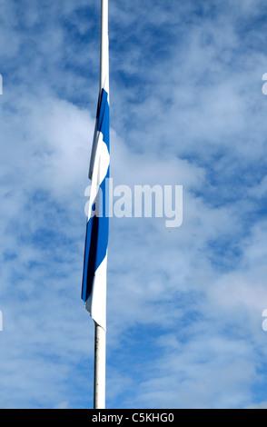 Half-staff Finnish flag in the wind - Stock Photo