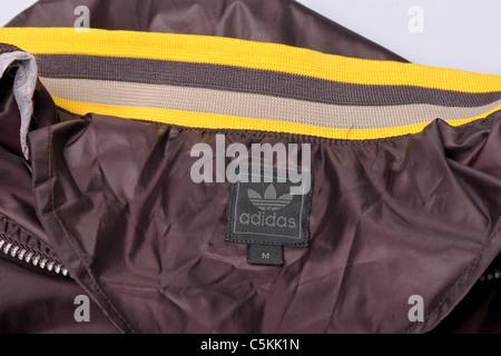Adidas sportswear men's overhead windcheater rain jacket in brown nylon 1/4 zip to neck overhead jacket. Label detail - Stock Photo