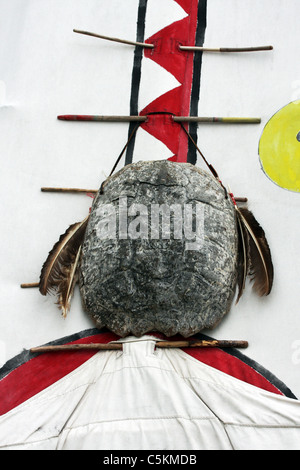 Giant turtle shell hanging as decoration on the front door of a Native American Indian teepee - Stock Photo