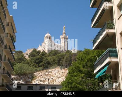 Church of Notre-Dame-de-la-Garde, Marseille, France, seen from below between apartment blocks - Stock Photo
