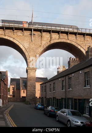 Train crossing a railway viaduct above a small street of terraced houses, Durham, County Durham, England, UK