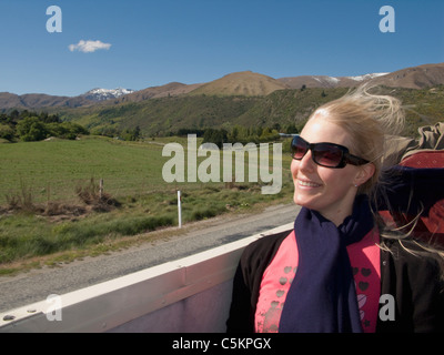 Blonde woman sitting in an open-top bus with wind in her hair, Queenstown, New Zealand - Stock Photo