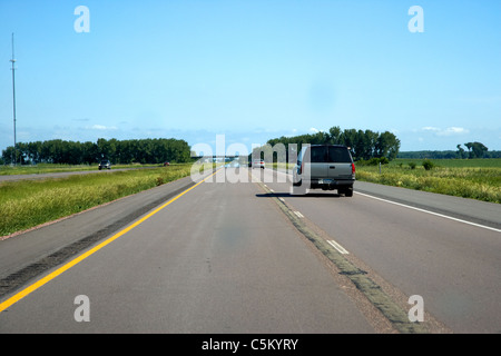 driving along interstate in south dakota usa with heat haze mirage in the distance - Stock Photo