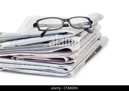 A pair of reading glasses on top of a pile of newspapers - Stock Photo