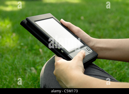 Young woman reads electronic book sitting on the grass. Shallow depth of field. - Stock Photo
