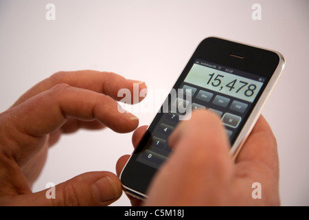 Man using calculator application on iPhone - Stock Photo