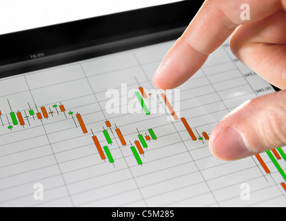 Touching stock market graph on a touch screen device. - Stock Photo