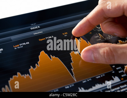Analyzing Stock Market Chart on Digital Tablet PC - Stock Photo