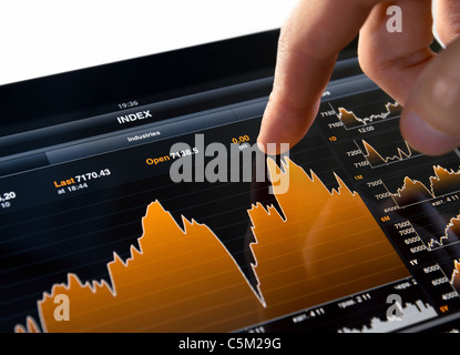 Touching Stock Market Chart on Digital Tablet PC - Stock Photo