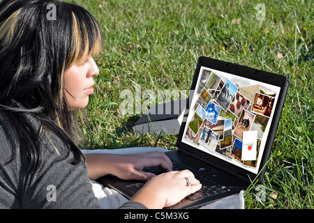A young woman viewing or editing a gallery of photos on her laptop computer. - Stock Photo