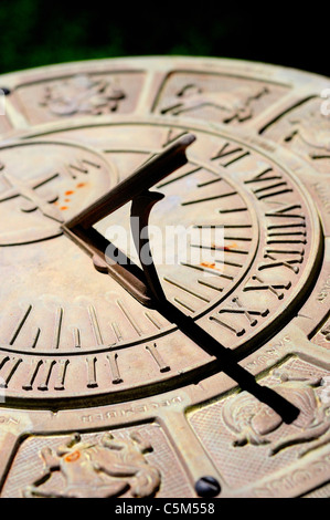 Sundial with Zodiac signs and figures surrounding Roman numeral times - Stock Photo