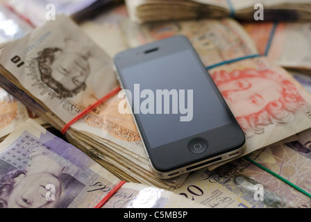 An Apple iPhone 4 with a blank screen lying on top of a very large number of British banknotes. - Stock Photo