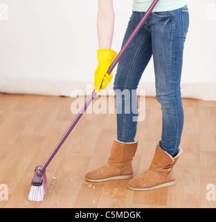 Attractive red-haired woman sweeping the floor at home - Stock Photo