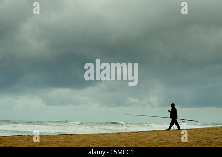 Angler walking by the beach in cloudy day - Stock Photo