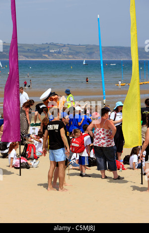 School children on the beach at Weymouth taking part in an outdoor education class - Stock Photo