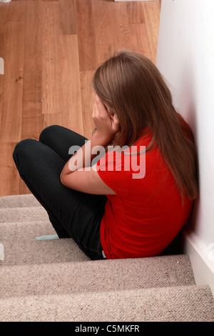 Young blonde female sitting alone on the stairs hands covering her face, back view. - Stock Photo