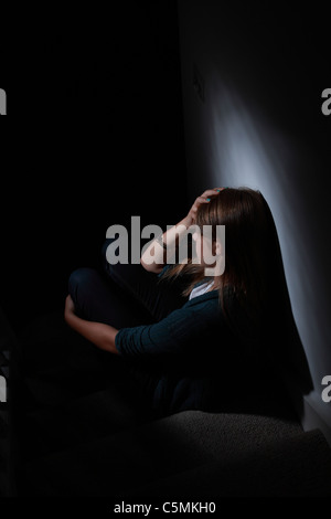 Young blonde female sitting alone in the dark, hand on head, back view.