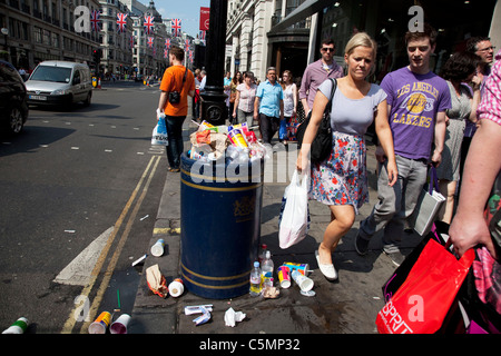 Overflowing rubbish bin and litter on Regent Street, central London. - Stock Photo