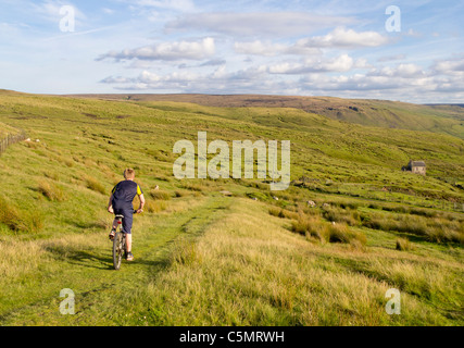 Boy mountain cycling at Brun Clough on Marsden Moor in the Pennines, England, UK; Yorkshire - Lancashire border - Stock Photo