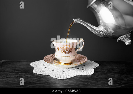Pouring freshly brewed tea from a silver teapot into a vintage fine bone china tea cup. - Stock Photo