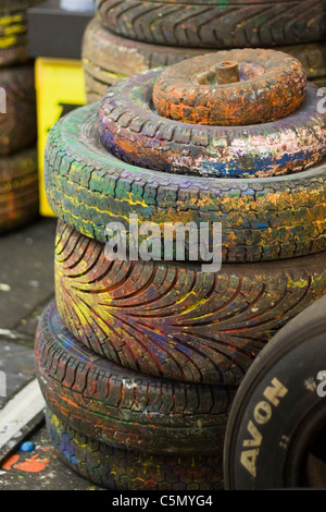 A Stack of Tires Painted in different colours - Stock Photo