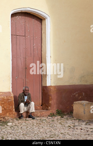 Cuba, Trinidad. Old Man Sitting on Door Stoop. - Stock Photo