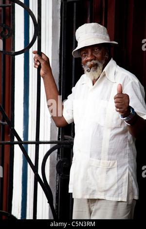 An elderly man standing outside a Cuban cigar factory smoking a Cuban cigar Havana Habana Cuba - Stock Photo