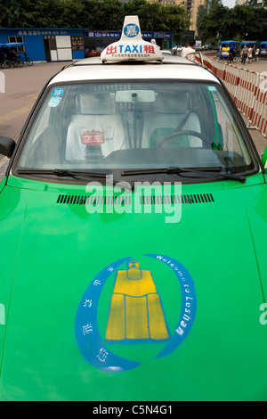 Taxi cab (front / bonnet) waiting for passengers / fare on rank outside the bus station in Leshan city, Sichuan - Stock Photo