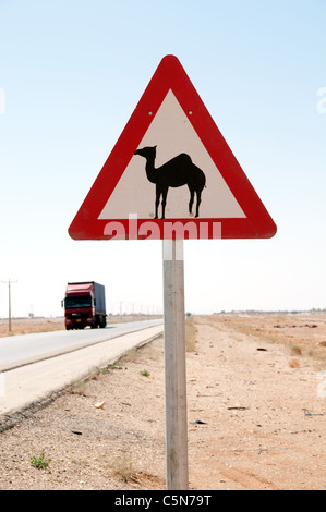 A camel crossing and warning road sign on highway 40, the desert road connecting Amman and Baghdad, in the eastern - Stock Photo