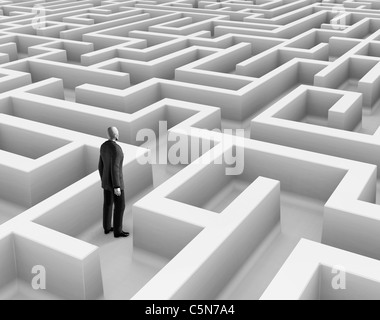 Man wearing a suit standing in maze. - Stock Photo