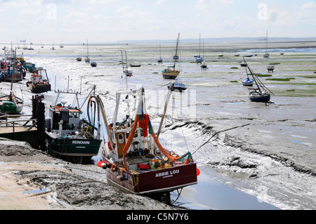 Cockle & shellfish fishing boat moored in Thames Estuary on mud flats low tide creek Old Leigh Essex coast Kent - Stock Photo