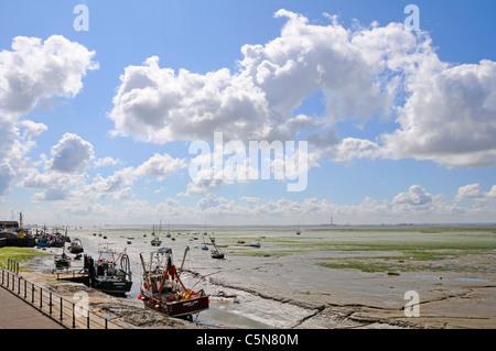 Thames Estuary low tide landscape boats & mud flats at Leigh on Sea Essex Coast England UK with Kent coastline horizon - Stock Photo