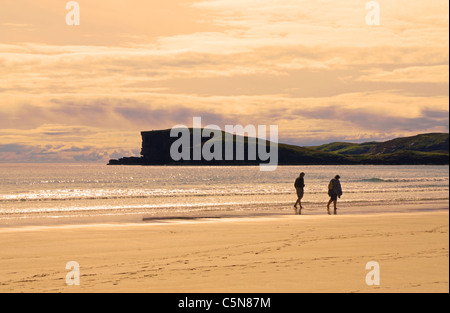 A couple strolling barefoot along the water's edge at Oldshoremore beach, evening, near Kinlochbervie, Sutherland, Scotland, UK