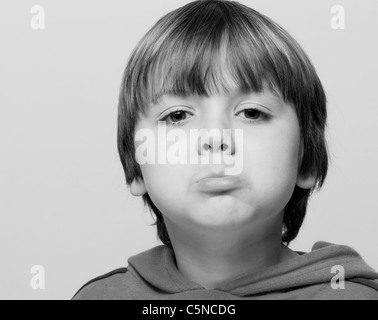 Portrait of a young boy, sulking - Stock Photo