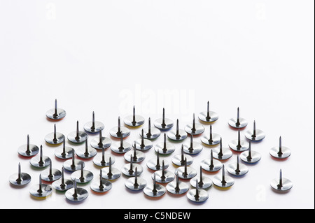 Drawing pins on a white surface - Stock Photo