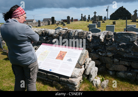 A tourist reads an interpretative sign at Cladh Mhuire chapel and graveyard on Benbecula in the Outer Hebrides - Stock Photo