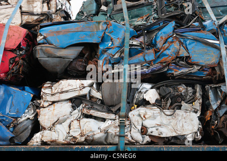 A pile of crushed car bodies strapped onto a transporter. - Stock Photo