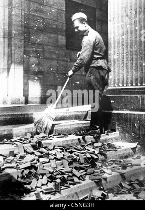 Russian soldier cleans Nazi propaganda material, the Reichstag, Berlin, Germany, World War II, 1945 - Stock Photo