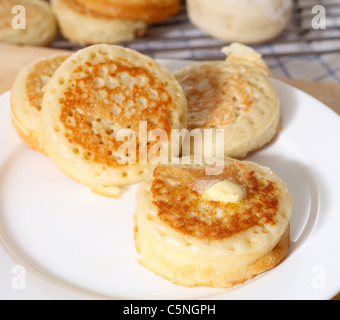 Traditional English homemade crumpets with a knob of butter on the front one. - Stock Photo