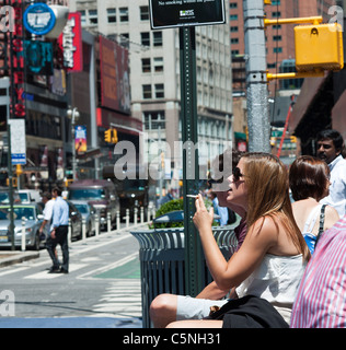 A smoker in a pedestrian plaza in Times Square in New York - Stock Photo