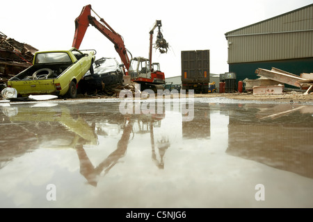 Scrapyard crane lifting scrap metal and cars for recycling reflected in water, uk - Stock Photo