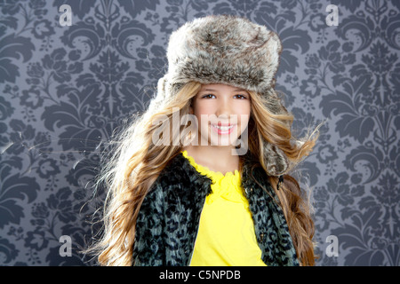 children fashion girl with winter leopard coat and fur hat on retro background - Stock Photo