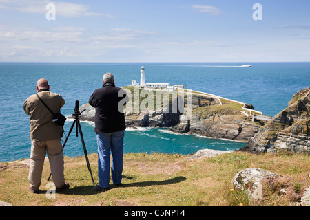 Birdwatchers using binoculars to sea watch and spot birds on cliffs with South Stack lighthouse on Ynys Lawd Holy - Stock Photo