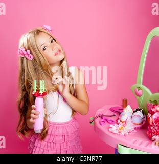 hairdresser blond fashion doll girl with hair curler in pink vanity mirror - Stock Photo