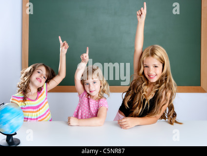 kids student clever girls group in classroom raising hand finger with blackboard - Stock Photo