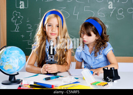 children girls at school classroom with world map and microscope - Stock Photo