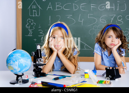 Bored student kids at school classroom in desk with blackboard - Stock Photo