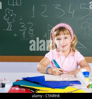 happy similing children student girl at school classroom desk - Stock Photo