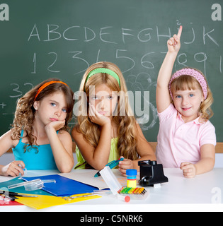 boring sad student with clever children girl raising hand finger at school classroom - Stock Photo